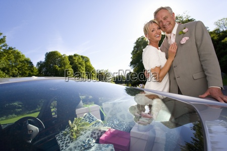 senior bride and groom by car