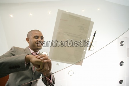 businessman by pen and paperwork on