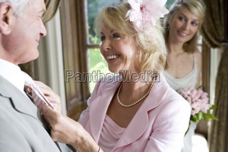 mature woman adjusting husbands tie bride
