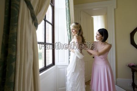 bridesmaid adjusting brides dress smiling side