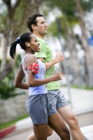 couple wearing sportswear jogging on pavement