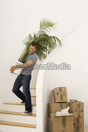 man moving house carrying large pot