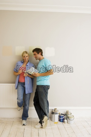 couple decorating at home man holding