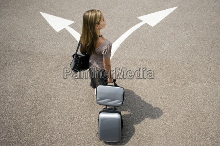 businesswoman standing with luggage in car