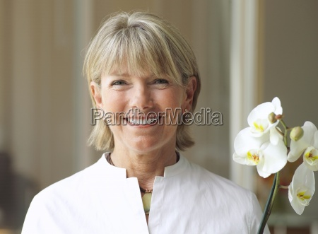 mulher senior que prende a flor