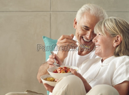 senior couple relaxing on sofa at