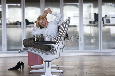 businesswoman stretching in airport waiting area