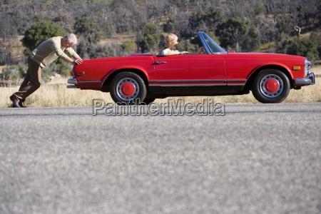 man pushing broken down red convertible