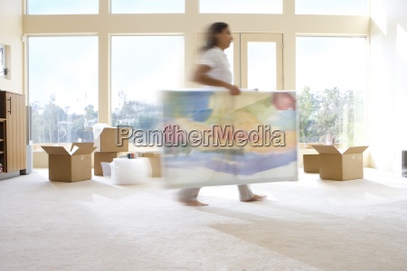 woman carrying artwork in new home