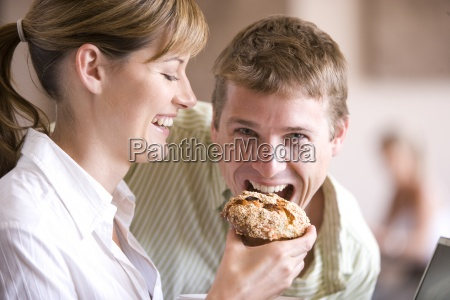 woman feeding boyfriend muffin