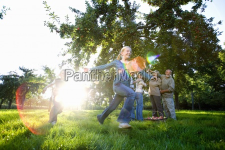 family of three generations in orchard
