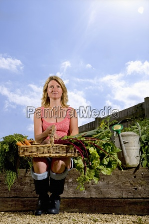 woman sitting in organic garden holding