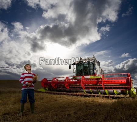 boy standing next to combine harvester