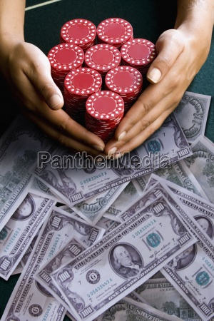 woman reaching for poker chips on