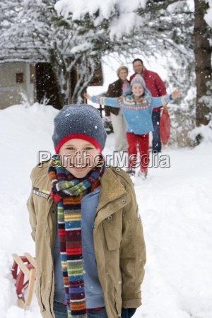 portrait of young boy pulling sled