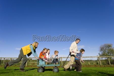 mother and father pushing children in