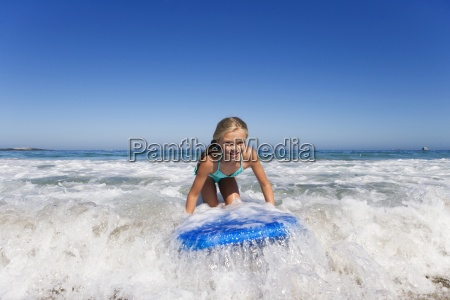smiling girl surfing on body board