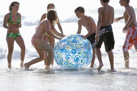 kids wading in ocean and playing