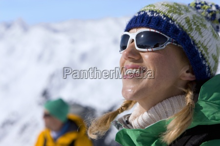 happy woman enjoying sunshine on snowy