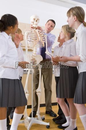 school children listening to biology teacher