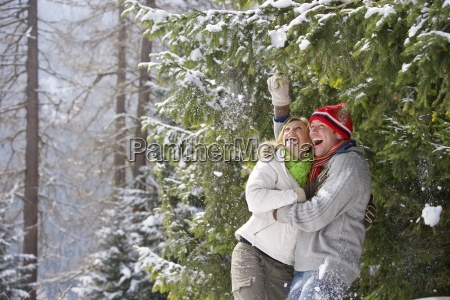 playful couple laughing in snow covered