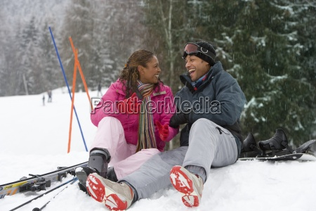 mixed race couple sitting in snow