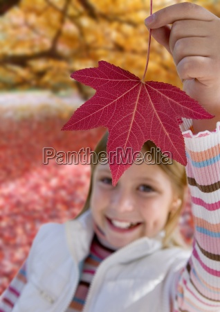 girl lifting red leaf in autumn