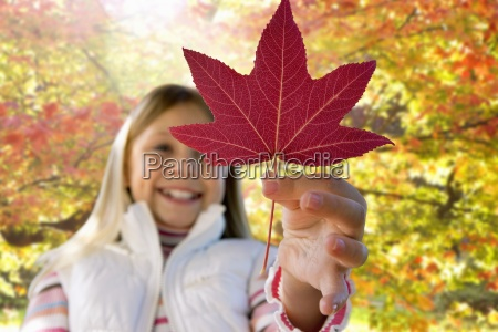 girl holding red leaf in autumn