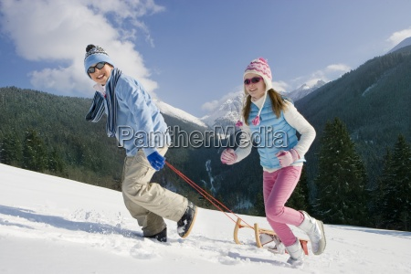 brother and sister pulling sled uphill