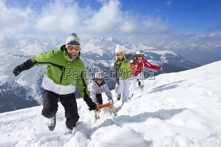 family pulling sled uphill in snow