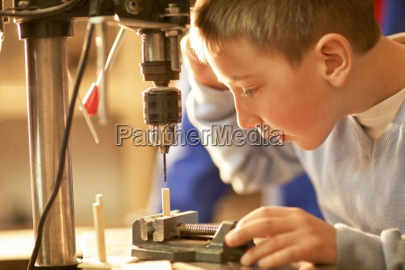 young boy using drill on craft