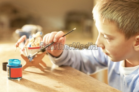 young boy painting wooden craft
