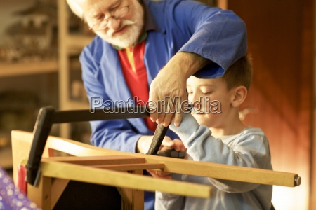grandfather and grandson making wooden craft