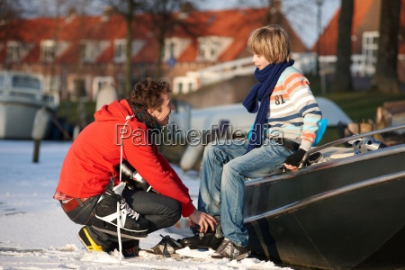 father helping son put on ice