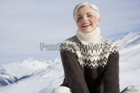 happy mature woman sitting in mountains