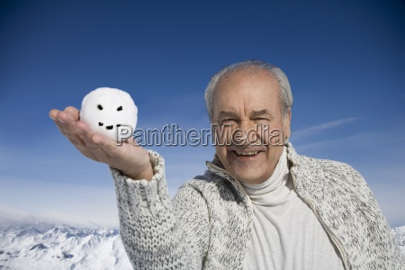 senior man holding snowball with smiley