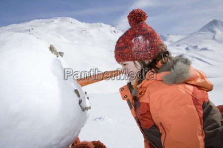 young girl rubbing nose against snowman