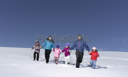 mid adult family running through snow