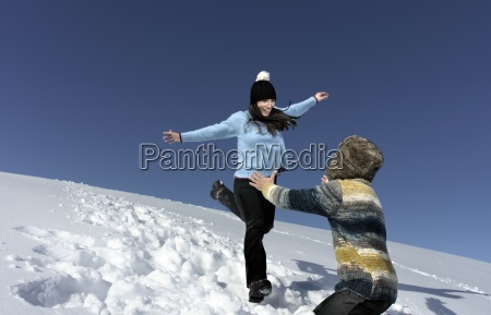 mid adult couple playing in snow