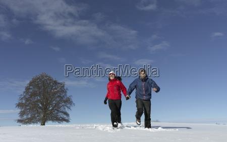 mid adult couple running through snow