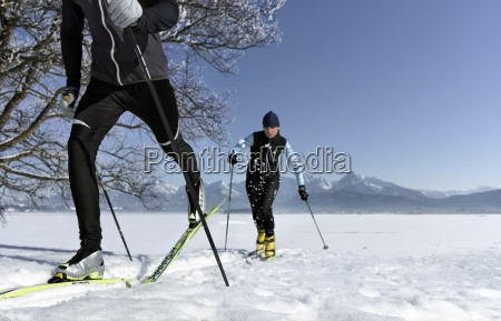 mid adult couple cross country skiing