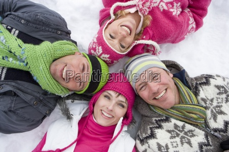 smiling family laying in snow in