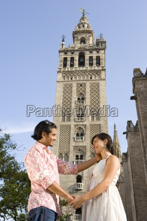 young couple holding hands by tower