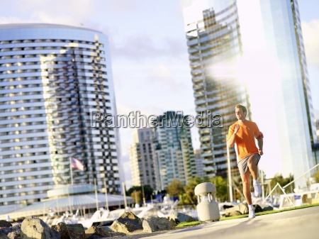 young man running by skyscrapers low