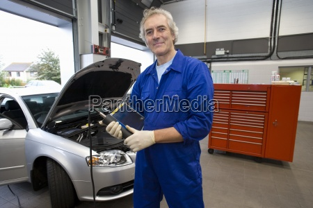 mechanic with electronic diagnostics device by