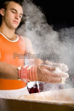 male gymnast coating hands in powder