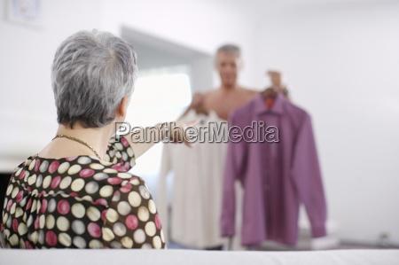 senior woman pointing at shirts that