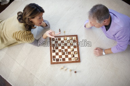 mature couple playing chess high angle
