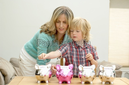 mother and son putting coin in