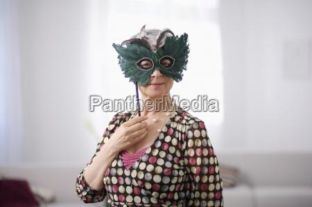 portrait of senior woman wearing masquerade